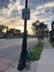 An image of a DDOT bus stop with a bike leaning against it. It is morning and the clouds are luminous with sunlight