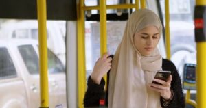 A young hijabi reading her smartphone on the bus