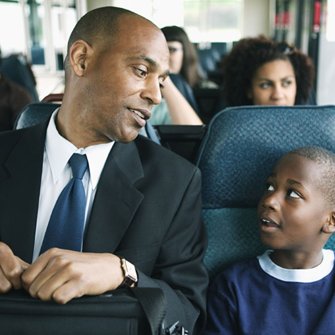 A Black dad and son looking at each other on a bus.
