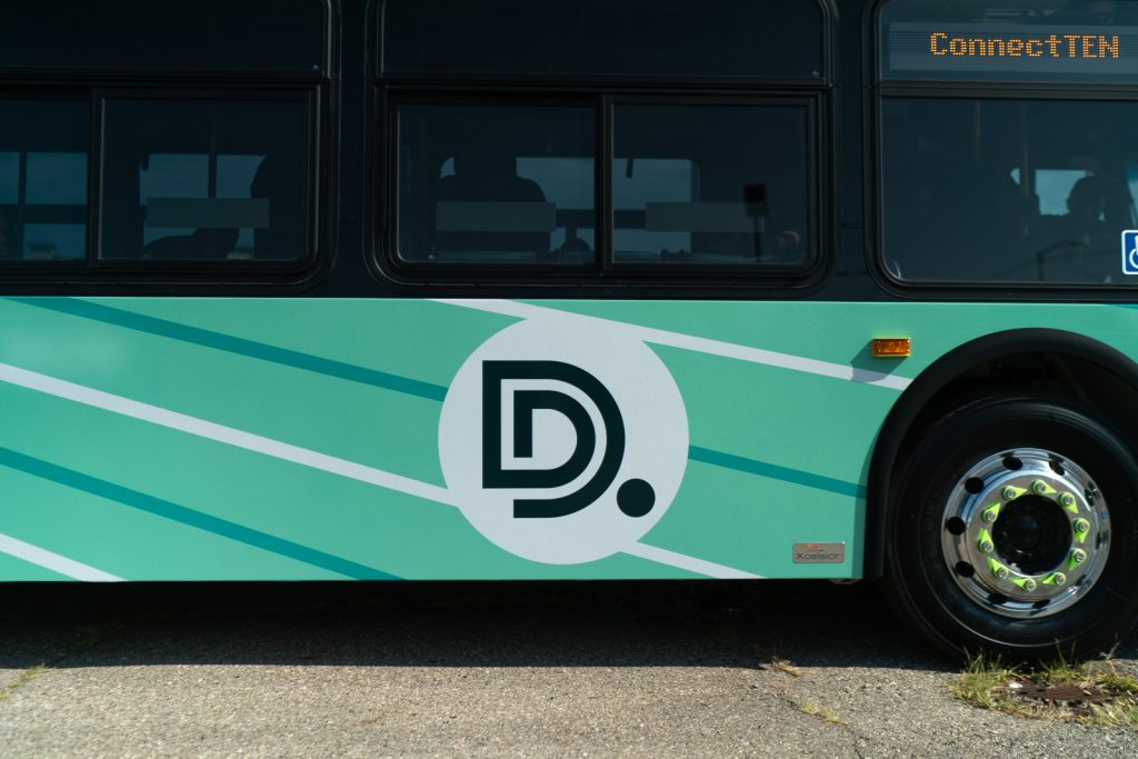A photo of the side of a new DDOT bus, showing the logo with green lines behind it.