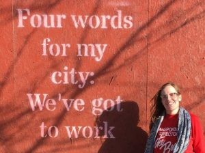 "A woman with long hair smiles into the camera. Stenciled on plywood next to her are the words ""Four words for my city: We've got to work"""