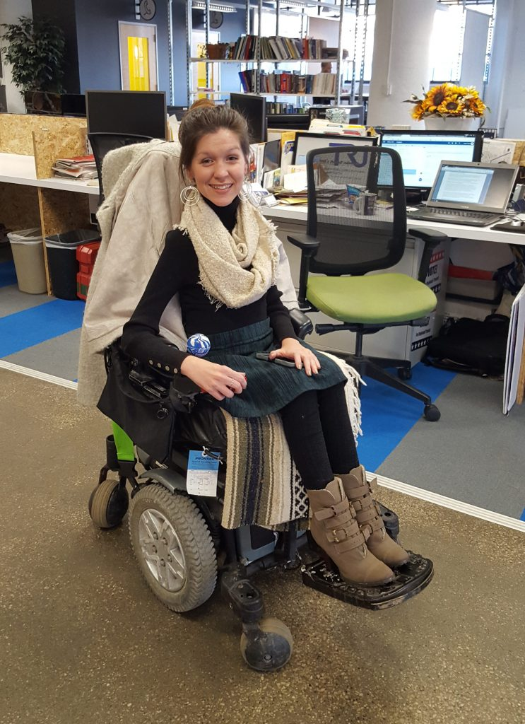 Kristen in her power wheelchair working at the TRU office