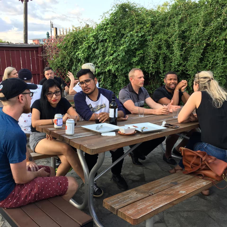 A diverse group of people talking with each other sitting at a picnic table on an outdoor patio