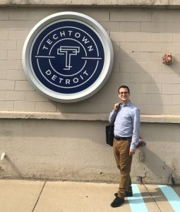 A man in a blue shirt and khakis stands smiling on a sunny sidewalk next to the circular TechTown Detroit logo posted on the wall.
