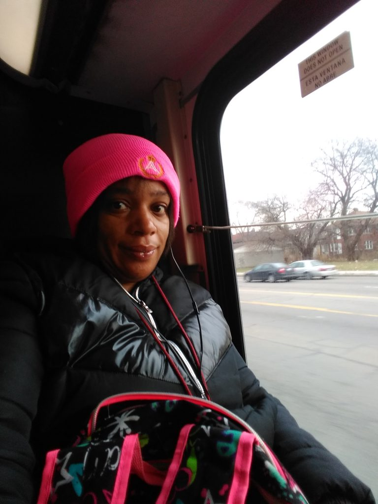 Tonika Williams sitting on a bus next to the window. She is looking at the camera. Her hat and the trim of her backpack are the exact same shade of hot pink.