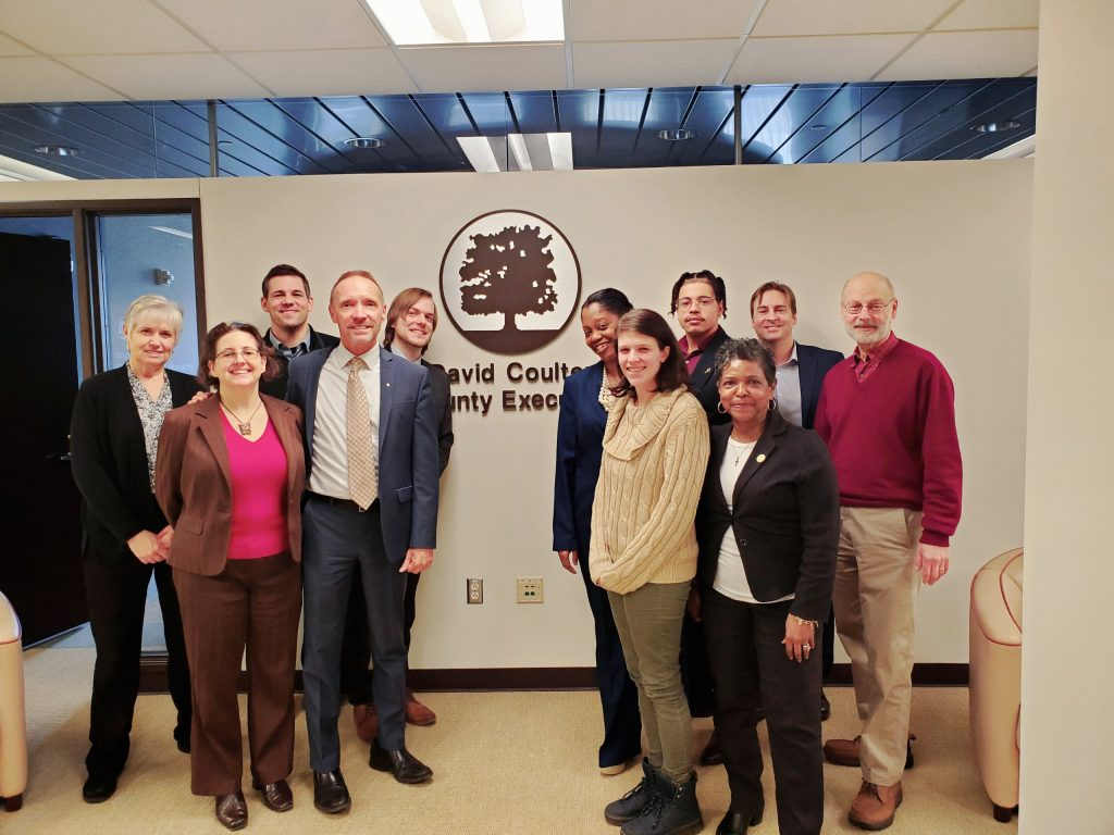 Twelve people stand in front of the Oakland County Executive crest, including County Executive Dave Coulter and TRU's Megan Owens